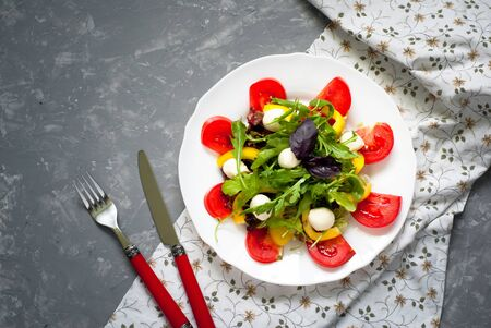 peppar: Fresh summer salad. Salad from tomatoes, agaricus, lettuce, pepper and mozzarella. Grey beton background.