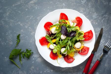 Beton: Fresh summer salad. Salad from tomatoes, agaricus, lettuce, pepper and mozzarella. Grey beton background.
