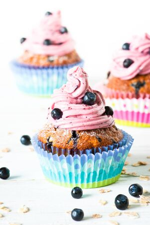 jimmies: Blueberry Cupcakes decorated with whipped cream frosting and fresh blueberries on a white background. Blueberry muffins with oat flakes.