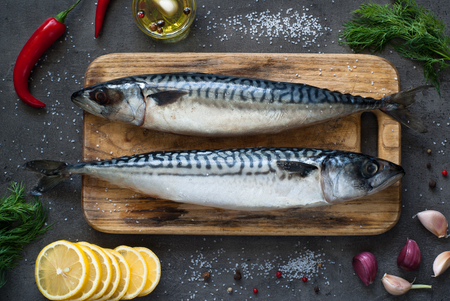 Fresh fish. Raw mackerel with salt, lemon and spices on a dark background. Imagens