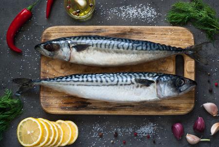 Verse vis. Ruwe makreel met zout, citroen en kruiden op een donkere achtergrond. Stockfoto