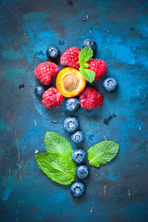 Fresh summer berries and fruits in the shape of flower on blue  background. Creative Fruit background.