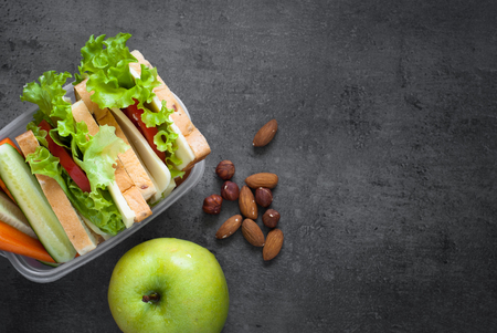 Lunch box with sandwich, vegetables, juice, nuts and apple on black background. Healthy eating. Flat lay. Banque d'images