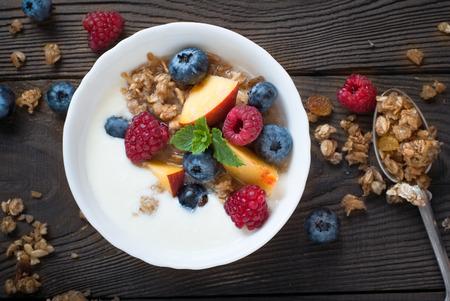 latte fresco: Yogurt with Granola  and fresh berries on  wooden table. Healthy breakfast.