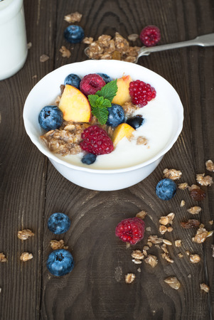 bawl: Yogurt with Granola  and fresh berries on  wooden table. Healthy breakfast.
