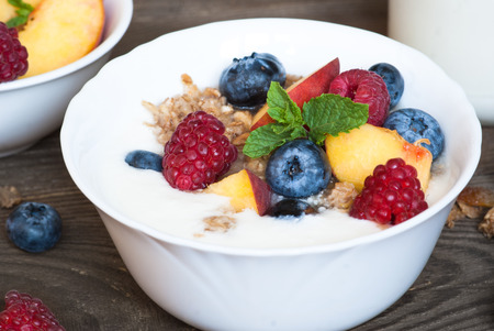 Yogurt with Granola  and fresh berries on  wooden table. Healthy breakfast.