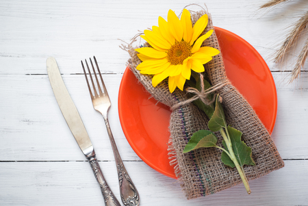 Autumn table setting with plate, silverware and sunflower on white wooden table. Top view. Thanksgiving