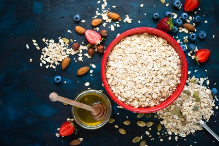 Ingredients for granola or oatmeal. Rolled oats, berries, bananas, honey, nuts. Healthy eating Flat lay
