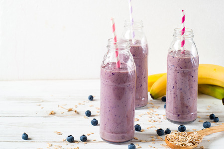 Blueberry smoothie or milkshake in the bottles on white wooden table. Dairy products. Eco food. Stock Photo
