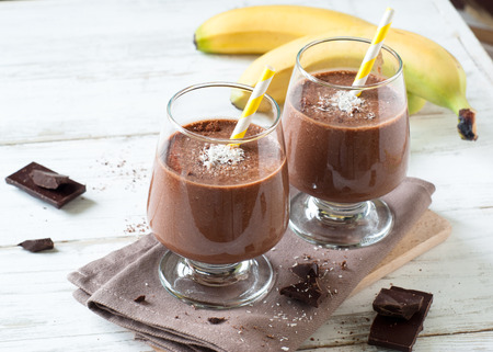 Chocolate banana smoothie or milkshake with coconut on white wooden table. Archivio Fotografico