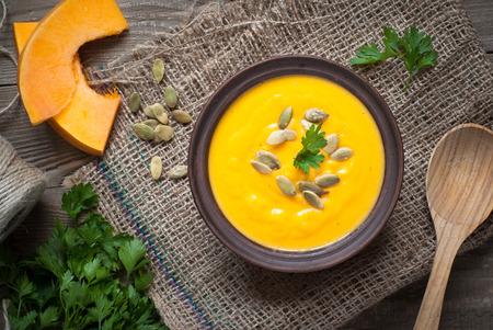 Sopa de calabaza tradicional con semillas de calabaza en la mesa de madera oscura.
