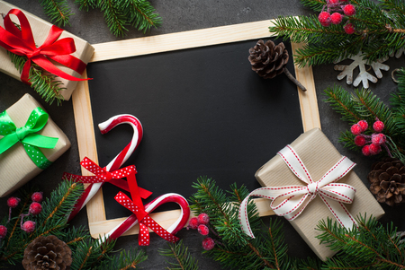 Christmas gift and decorations around chalkboard. Christmas present background with copy space.