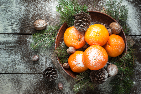 Tangerines, fir tree brunches, pinecones and nuts. Christmas food decorations. Table setting