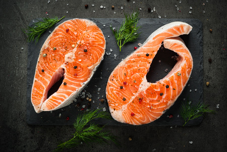 black dish: Raw salmon steak with sea salt and pepper. Fresh fish. Top view, copy space. Food background. Stock Photo