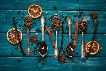 loose leaf: Various kinds of tea in spoons on blue wooden background. Dry Tea assortment.