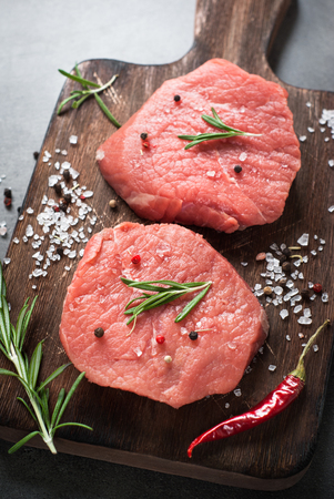 Raw meat. Raw beef steak on a cutting board with herbs and spices. Top view with copy space.