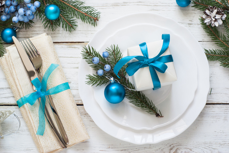 Christmas table setting with decorations on white.