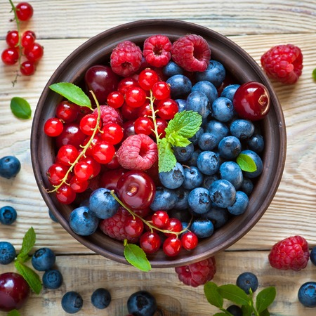 cheery: Fresh berries. Various  summer berries in a bowl on rustic wooden table.