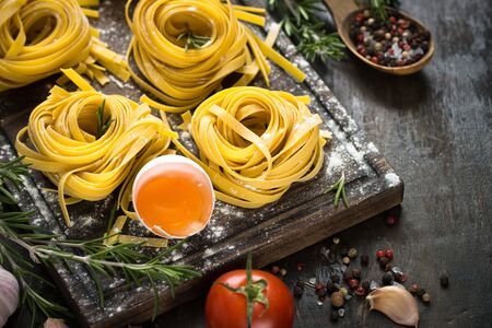 Fresh raw pasta tagliatelle and ingredients for cooking . Italian food background.