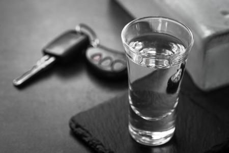 Vodka shot drink and car key. Dont drink and drive concept. Monochrome. Stock Photo