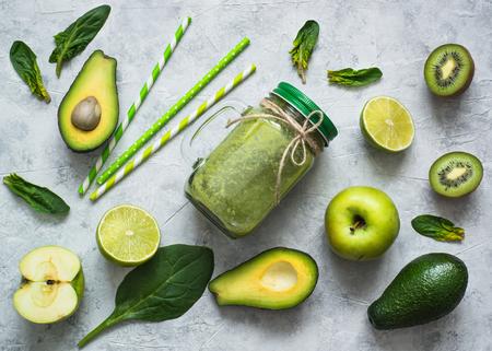 石工の瓶や食材で健康的な緑のスムージー。スーパー フード、デトックス、ダイエット、健康食品。ライム、リンゴ、ほうれん草、アボカド、ライ