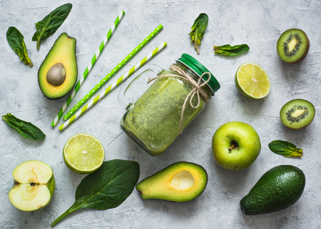 Healthy green smoothie in mason jar and ingredients. Superfoods, detox, diet, healthy food. Lime, apple, spinach, avocado and lime. Green food background Reklamní fotografie