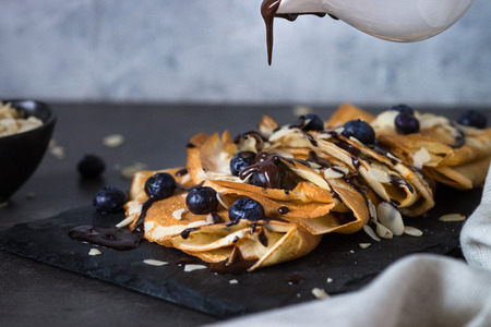 blini: Crepes with blueberries almond flakes and chocolate sauce on black slate plate.