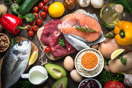 バランスの取れた食事食品背景。健康的な栄養の有機食品。料理の食材。暗い石のテーブルの上の平面図です。 写真素材