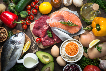 Balanced diet food background. Organic food for healthy nutrition. Ingredients for cooking. Top view over dark stone table.