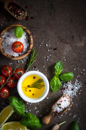 Food background with cooking ingredients  at dark stone table. Top view. Sea salt, pepper rosemary, basil and tomatoes. Stock Photo