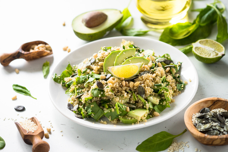 Fresh quinoa salad with spinach, avocado, greens, seeds and Pine nuts on white table. Clean eating detox and vegetarian food. Reklamní fotografie