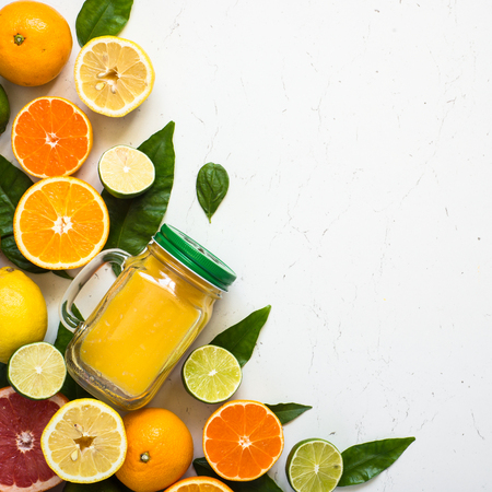Citrus juice smoothie and ingredients on white. Fruit food background. Healthy eating. Top view. Square.