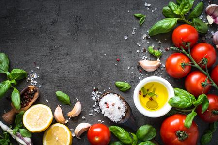 オリーブ オイルは、ハーブとトマトをスパイスします。料理の食材。黒いスレートのテーブルの食べ物背景。トップ ビュー コピー スペース。