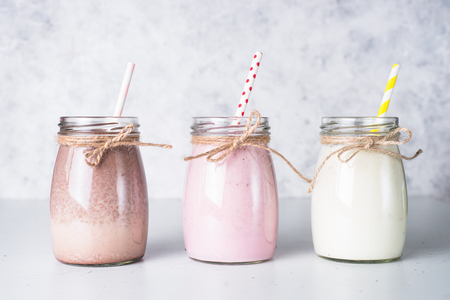 Set of milkshake in jars. Banana chocolate and strawberry milkshakes with nuts and coconut. Summer dessert. Healthy food.
