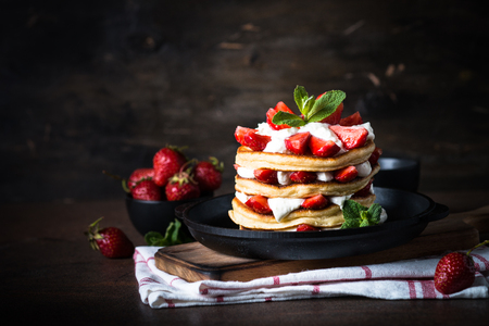 Pancakes cake with mascarpone and strawberries. Dark rustic background.