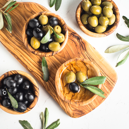 Black and green olives in wooden bowls and olive oil bottle. Top view on white background.