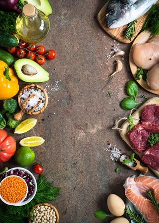 バランスの取れた食事食品背景。健康的な栄養の有機食品。肉・魚・豆と野菜。暗い石のテーブルの平面図です。