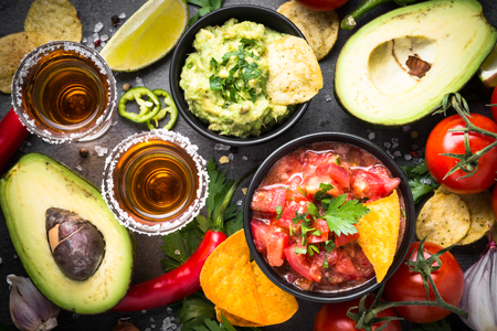 Latinamerican food party sauce guacamole, salsa, chips and tequi Stock Photo