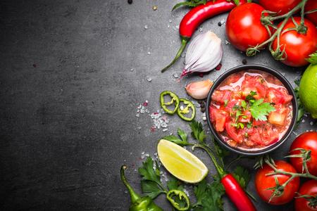 Tradycyjny latynoamerykański meksykański sos salsa i składniki na czarnym kamiennym stole. Przestrzeń kopii widoku z góry.