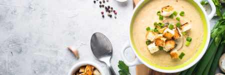 Creamy Mushroom Soup with croutons on gray  concrete table. European cuisine. Long banner format. Banco de Imagens - 82070626