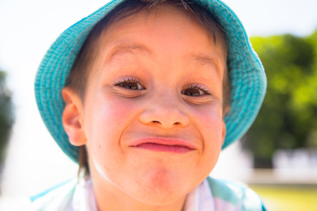 Happy child outdoor. Little boy with funny face in th park. Foto de archivo