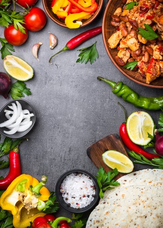 Cooking Mexican taco with meat beans and vegetables at black stone table. Latin american food background. Vertical. Banco de Imagens
