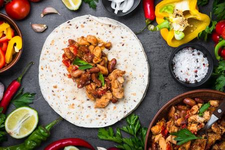 tortilla de maiz: Cocinar el taco mexicano con los frijoles de la carne y las verduras en la tabla negra de la pizarra. Fondo latinoamericano de la comida. Vista superior. Foto de archivo