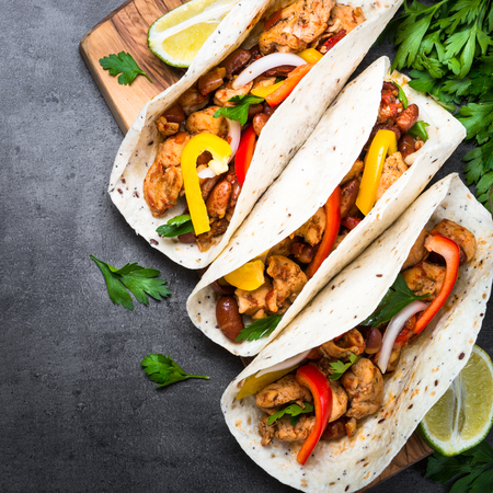Mexican taco with meat beans and vegetables at black slate table. Latin american food. Top view. Square. Stock Photo