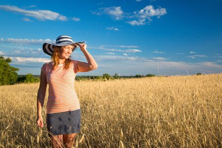 Young woman in the field. Yellow ears  blue sky and sunset.