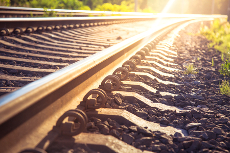 Rails and railway going into the distance against the sunset. Boltless fastening of rails. Stock Photo