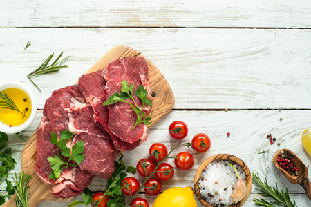 table top: Fresh meat. Raw Beef steak with ingredients on white wooden table. Top view copy space.