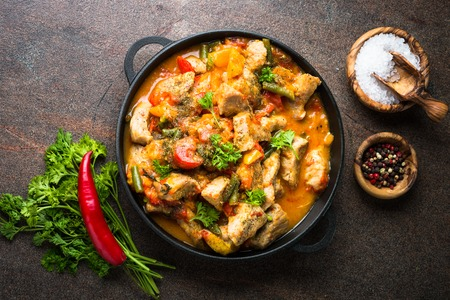 Stewed pork with vegetables in tomato sauce in a cast-iron pan. Top view on dark stone background. Stock Photo