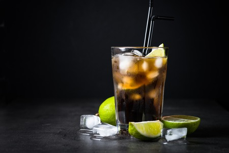 Cuba libre on dark background. Traditional summer alcohol iced drink. Stok Fotoğraf
