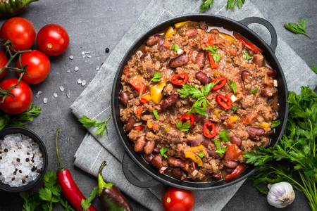 Chili con carne in a cast iron pan on dark stone table. Traditional mexican food. Top view. Stock Photo